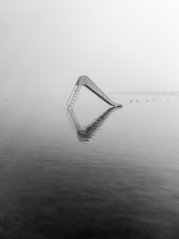 A white slide in the middle of water on a misty morning. Kralingse Plas, Rotterdam.