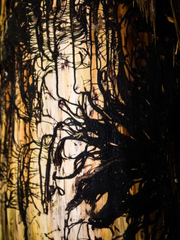 Rest of plants embrace a tree trunk, their black fibers trace lines like a painting on a golden trunk.